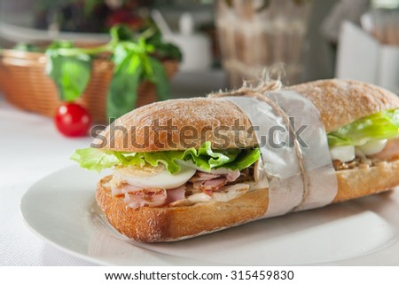 Close up Fresh sandwich with wheat bun, ham, sliced egg and lettuce leaves on the white round plate on the  restaurant table with colourfull ingredients - stock photo