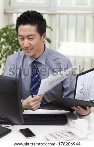 Close-up of a businessman using a laptop in an office