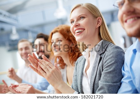 Close-up of a businesswoman applauding at the meeting on the foreground  - stock photo