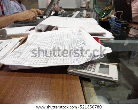 Close up of a table in a meeting room with documents and computers