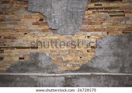 close up of  chipped brick wall /  peeling stucco - stock photo