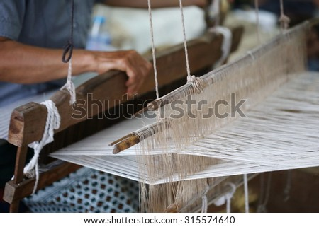 Close up of gold silk weaving on loom - stock photo