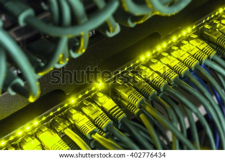 Close up of green network cables from data center connected with patch cord to black switch glowing in the dark. Blurred frame vignetting  - stock photo