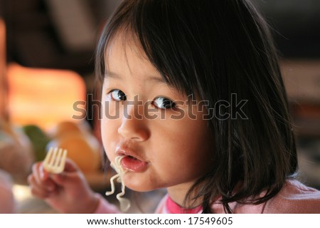 close up of hungry child eating pasta