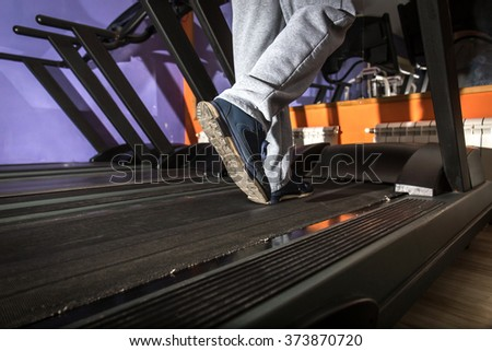 Close-up of man legs running by treadmill in sports club , row of treadmills - stock photo