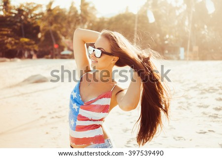close-up portrait of a beautiful young brunette in sunglasses girl on a sunny day in the summer on the beach by the sea smiling at sunset in denim shorts and top with print US flag lifestyle  - stock photo