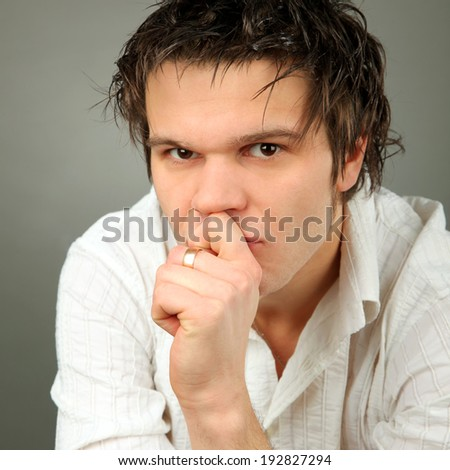 Close-up Portrait of adult man of sad man isolated on gray background  - stock photo