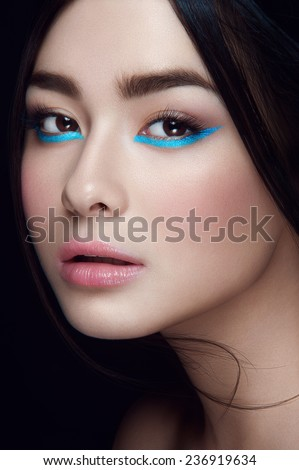 Close-up portrait of asian young girl with blue wings under hazel eyes and open lips with head to the left looking at you on black background - stock photo