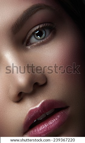 Close up portrait of belle young maiden with green eyes, natural make-up and rose lipstick, with head to the left looking at you and breathing through her open lips on dark background