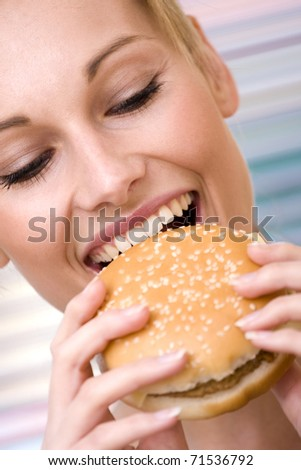 25-30 close-up portrait of young woman with hamburger focus on face