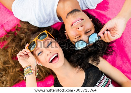 Close up summer portrait of  cheerful young couple  having fun and make grimace. Bright sunny colors .  Beautiful stylish girl and her  handsome man lying on mat. Wearing sunglasses .   - stock photo