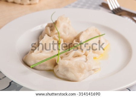 Close up tasty traditional asian steam dumplings with meat filling on a white plate on the serverd restaurant table - stock photo