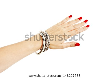Closeup hands of young woman with red manicure polished nails wearing many silver bangles and pearl bracelets. Isolated on white background - stock photo