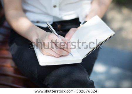 Closeup of a female hand writing on an blank notebook with a pen. - stock photo