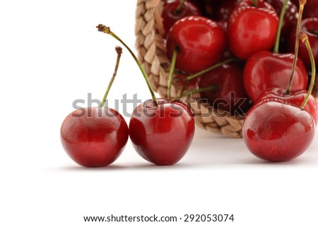 Closeup of red cherries in a basket on white background - stock photo