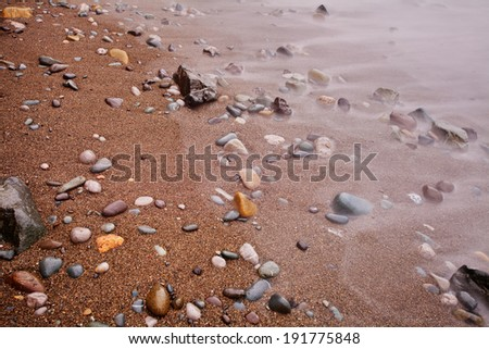 Closeup of sand and rocks with wave