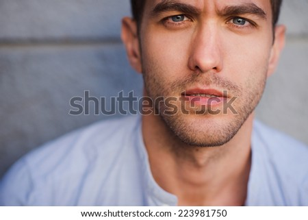 closeup portrait of a handsome young man standing outside - stock photo