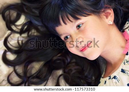 closeup portrait of beautiful little girl with curly hair and green eyes - stock photo