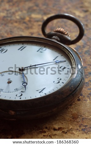 Closeup view of a silver pocket watch on old paper  - stock photo