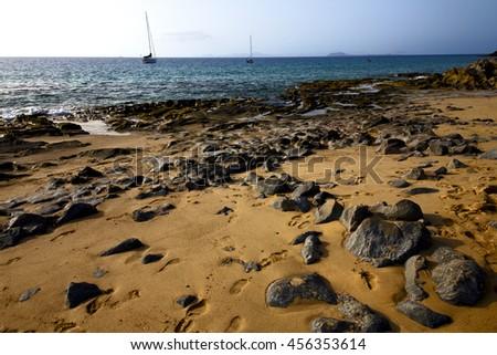 coastline rock beach  water boat yacht  and summer in lanzarote spain - stock photo