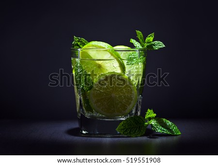 cocktail with lime , ice  and peppermint leaves