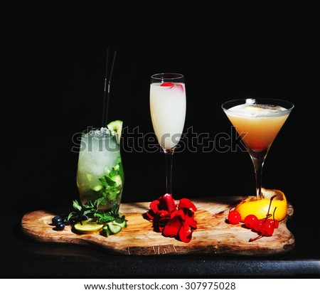 3 cocktails with beautiful garnish in a black background - stock photo