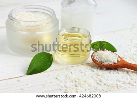 Coconut oil jar, coconut shavings spoon, fresh plant, white table. Natural skincare beneficial products. - stock photo