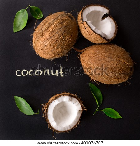 """Coconut"" poster. Coconut with green leaves isolated on a black background. Broken coconut."