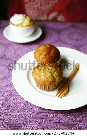 coffee and banana muffins in paper cupcake  with nuts on white plate,Dessert cakes with banana and coffee at table selective focus