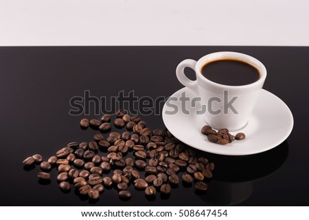 Coffee cup and beans on a black background and empty space for text.