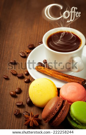 Coffee cup and macarone on a wooden table. Dark background. - stock photo