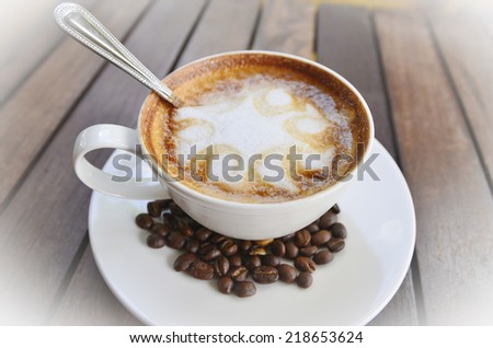 Coffee cup, cinnamon, anise on coffee beans, sweets on the plate, wood background, studio shot