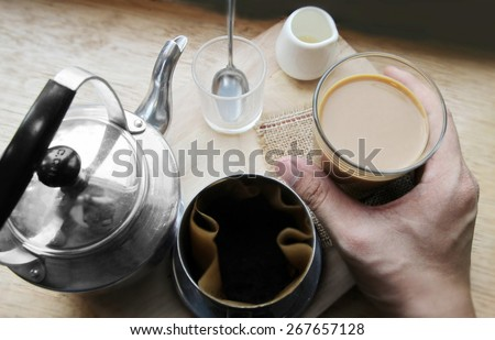 coffee dripping in vietnamese style on wooden table - stock photo