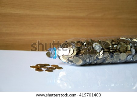 Coins in recycle plastic bottle on the desk