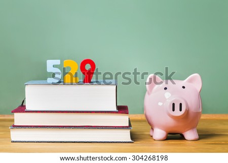 529 college savings plan theme with textbooks and piggy bank and green chalkboard background - stock photo