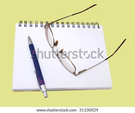 Color photograph of glasses and pen on the notebook. An isolated object on a yellow background.