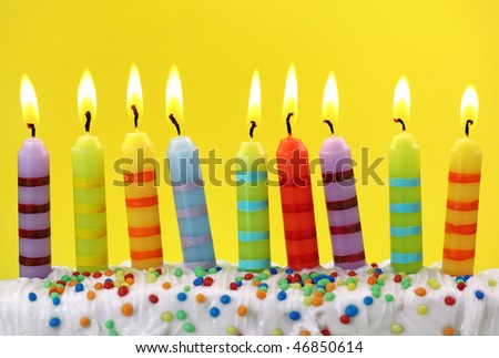 Colorful birthday candles on yellow background
