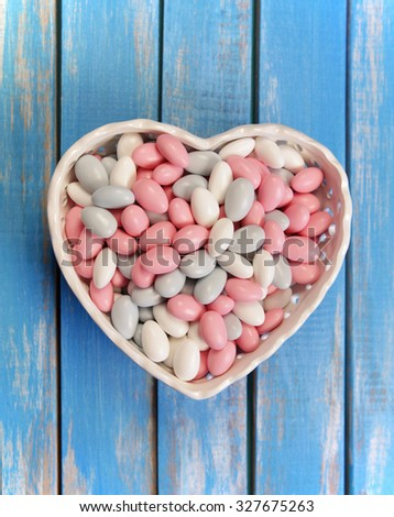 Colorful candy in white heart shaped bowl on wooden table .Top view from above