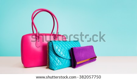 3 colorful fashion bags purses isolated on light blue background.  - stock photo