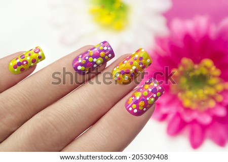 Colorful manicure with points on a lilac,yellow,pink,green background nails. - stock photo