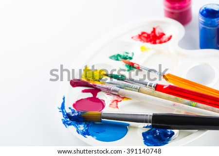 Colorful paints on palette and brushes on white  background  - stock photo