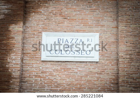 """Colosseum Square"" road sign in Ostia old town, Rome, Italy. Restored marble roman inscription, placed on brick boundary wall. Vignetting added for dramatic effect. - stock photo"