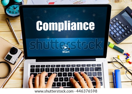 """""""Compliance"""" word on screen laptop with man hand work on it on wooden table with camera, spectacles, clock, pen and calculator - business, website, travel and blogging concept - stock photo"""