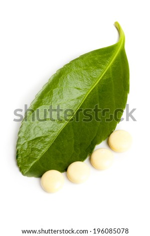 Concept of alternative medicine: Homeopathic natural pill and green leaf isolated on white background
