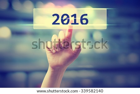 2016 concept with hand pressing a button on blurred abstract background  - stock photo