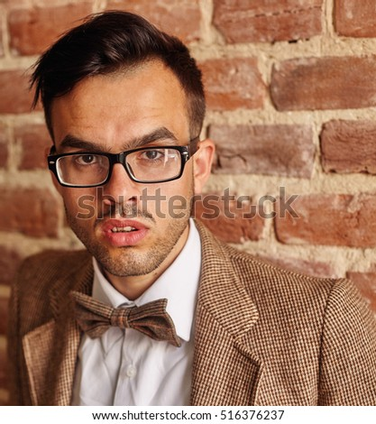 confident handsome young  man standing with his hands in his pocket against a brick background