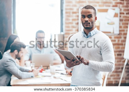 Confident in my team. Young handsome African man holding digital tablet and looking at camera while his colleagues discussing something in the background   - stock photo