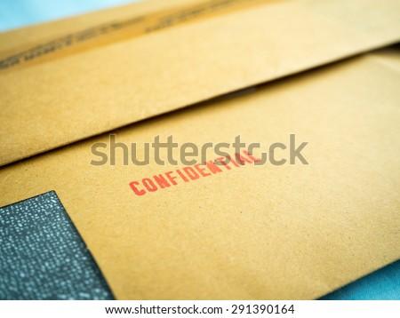 """Confidential"" printed on brown vintage envelope, in macro - stock photo"