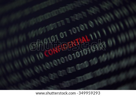 'Confidential' word in the middle of the computer screen surrounded by numbers zero and one. Image is taken in a small angle. Image has a spin blur effect applied to emphasize the word.