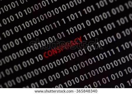 'Conspiracy' word in the middle of the computer screen surrounded by numbers zero and one. Image is taken in a small angle.